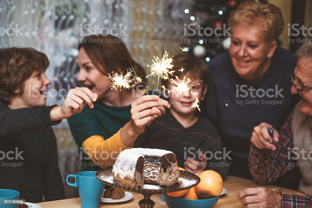 Happy family celebrate Christmas Eve with sparkles stock photo