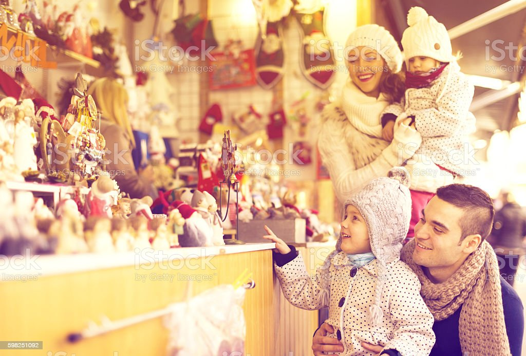 Happy family choosing Christmas decoration at Christmas market stock photo