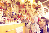 Happy family choosing Christmas decoration at Christmas market