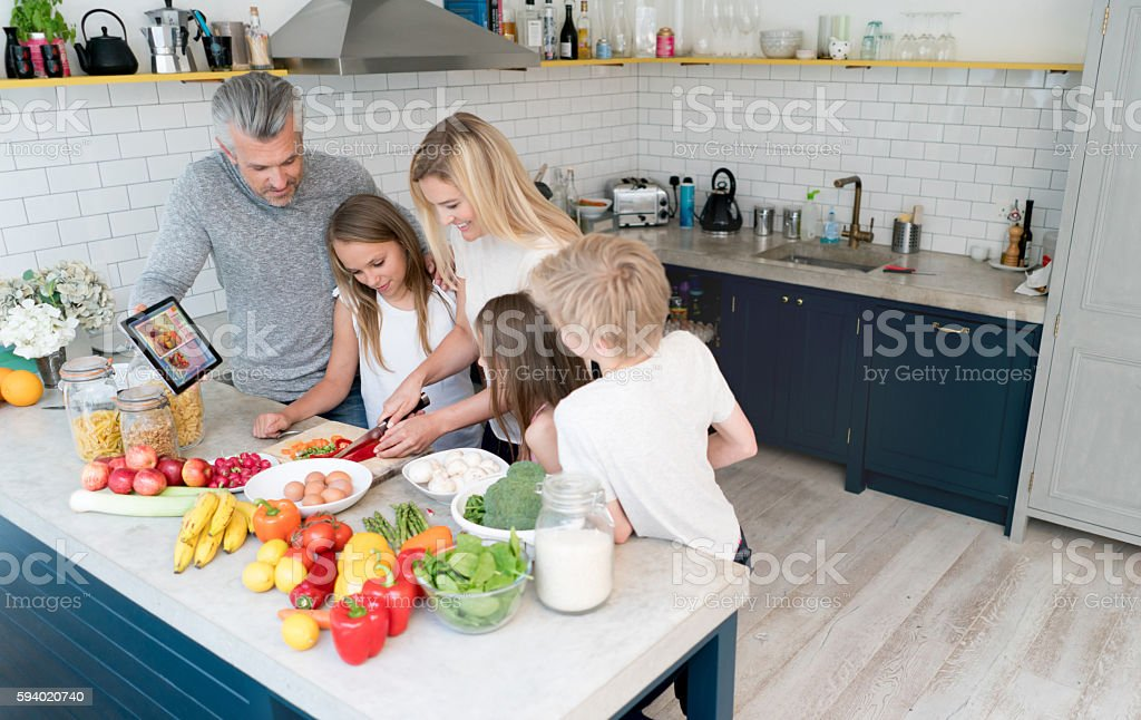 Happy family cooking at home stock photo