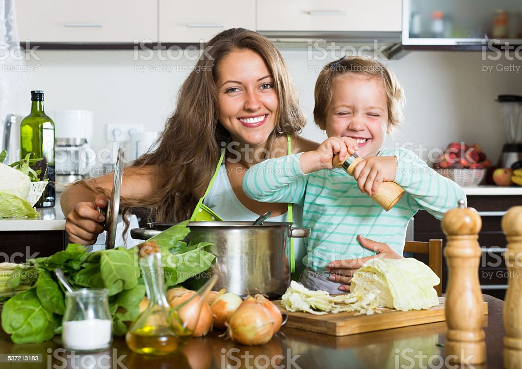 Happy family cooking soup stock photo