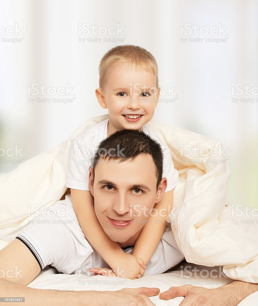 happy family. Dad and son playing in bed royalty-free stock photo