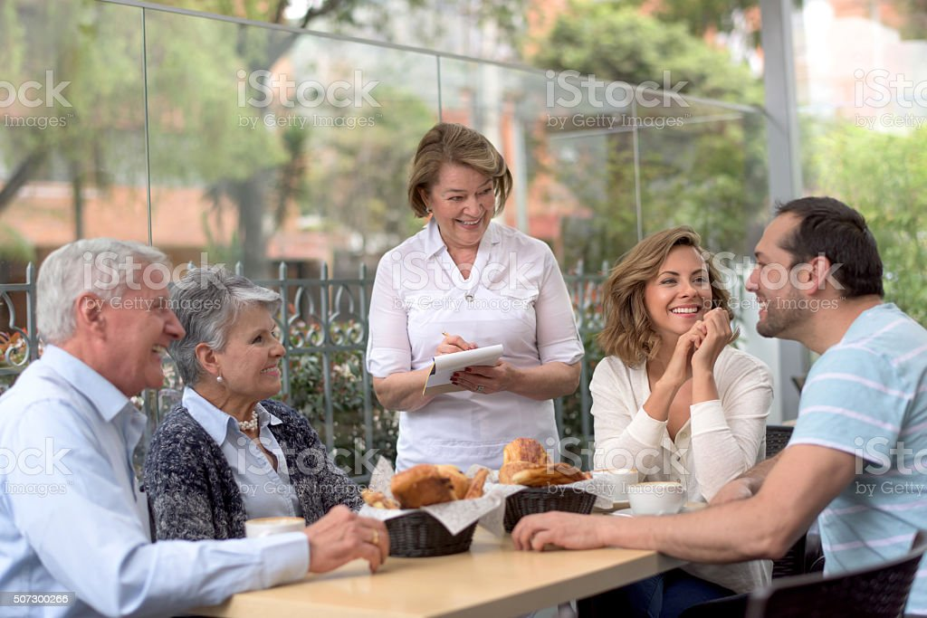 Happy family eating at a cafe stock photo