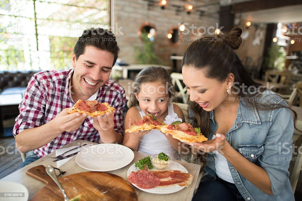 Happy family eating pizza at a restaurant stock photo