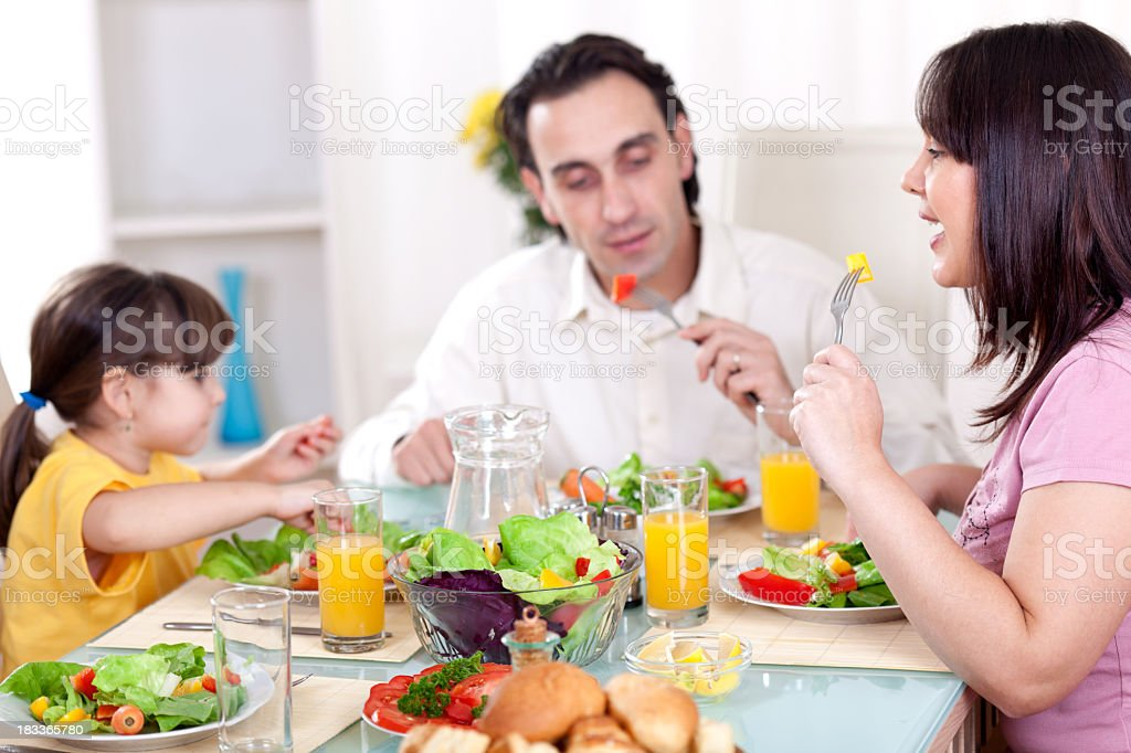 Happy family eating vegetables for lunch together royalty-free stock photo