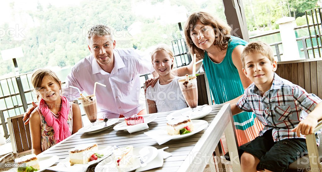 Happy family enjoying ice cream sundae and pastry stock photo