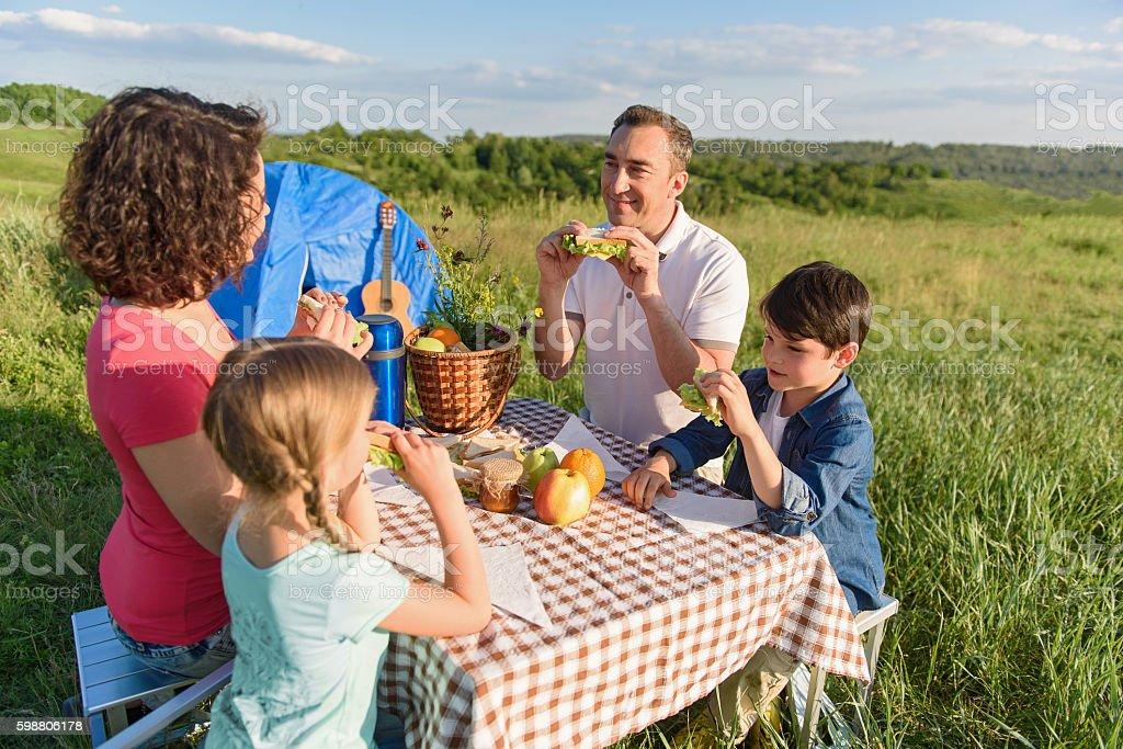 Happy family enjoying lunch outdoors stock photo