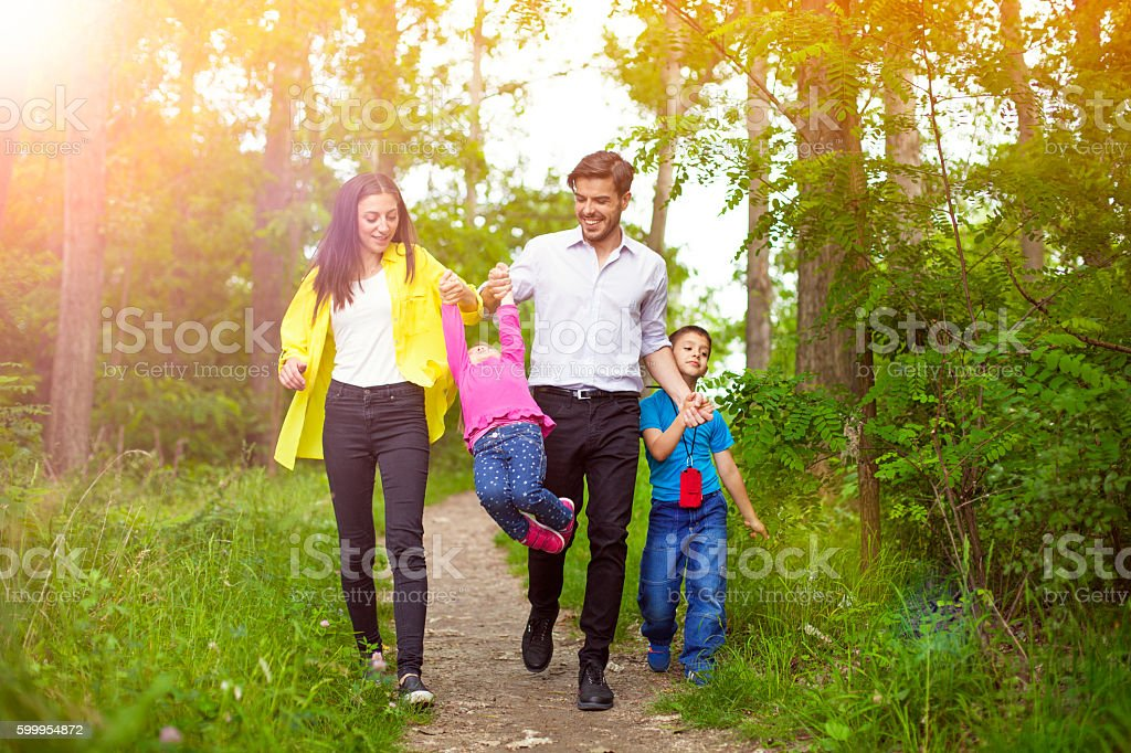 Happy family enjoying their summer day walk in nature. stock photo