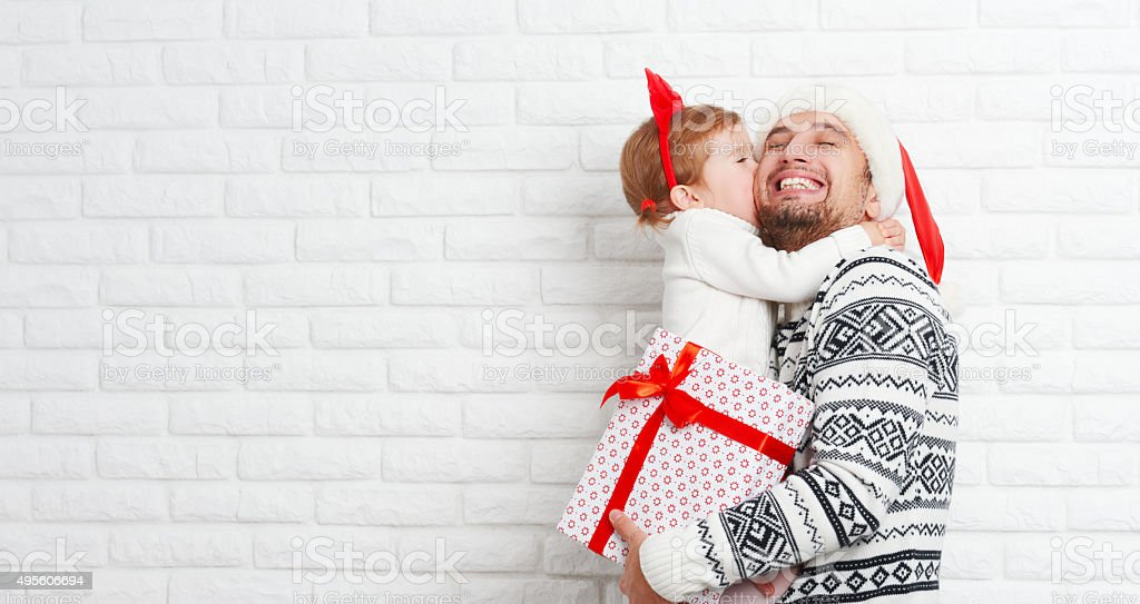 Happy family father and child with gift in Christmas kiss stock photo
