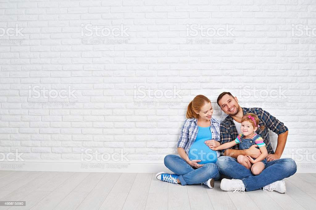 Happy family father and pregnant mother and child daughter near stock photo