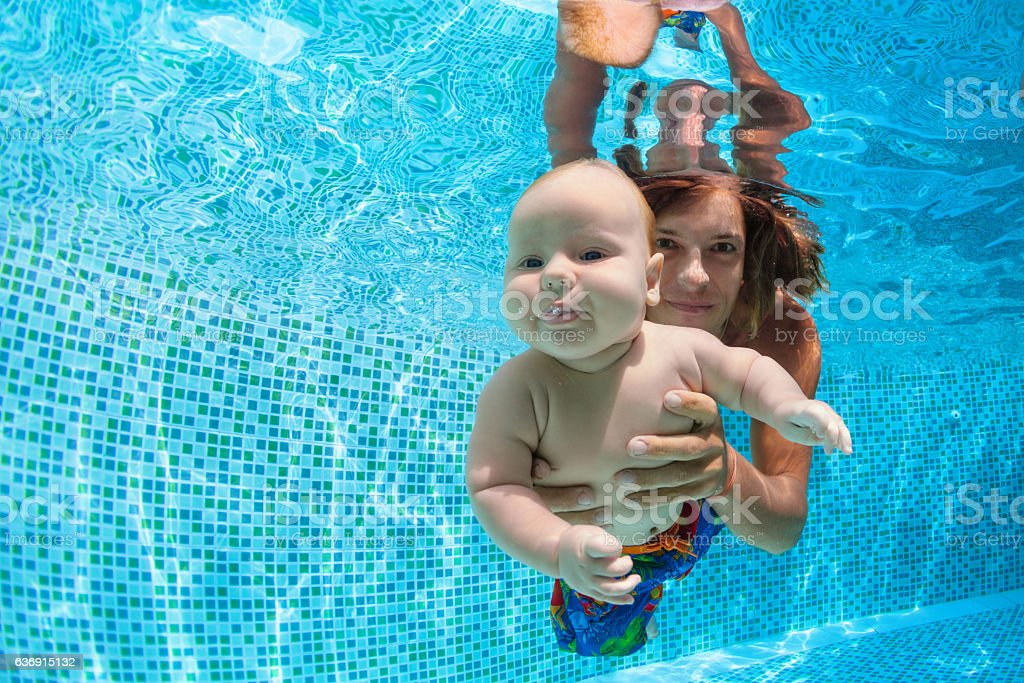 Happy family. Father, little son dive underwater in swimming pool stock photo