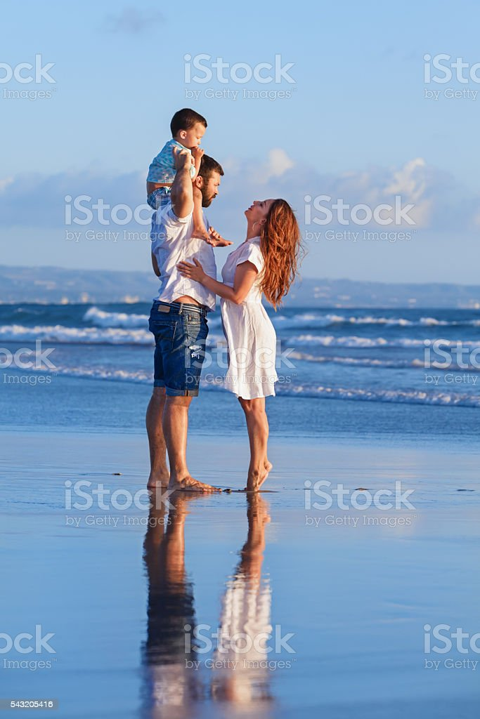 Happy family father, mother, baby son on sea beach holiday stock photo