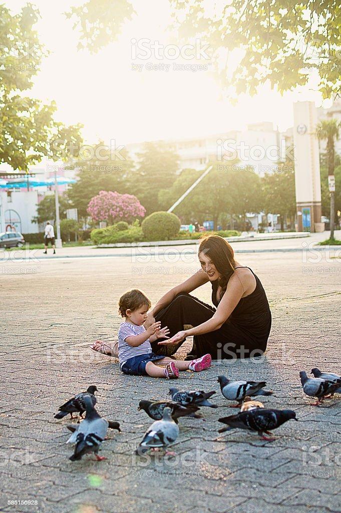 Happy family feeding birds stock photo
