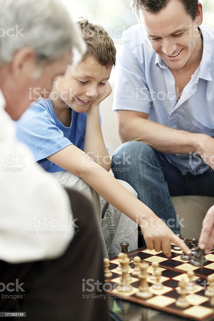 Happy family having a game of chess royalty-free stock photo