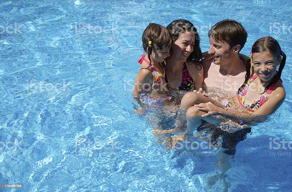 Happy family having fun in swimming pool stock photo