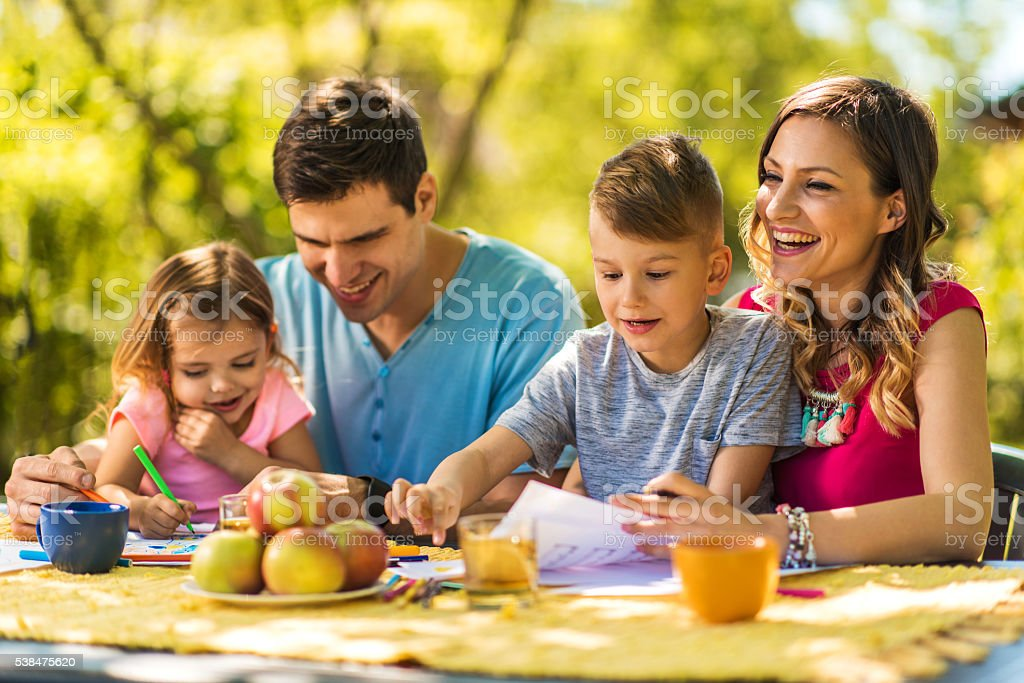 Happy family having fun outdoors and coloring together. stock photo