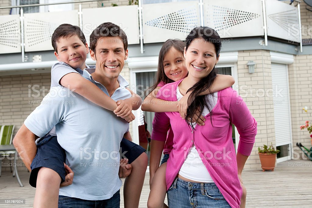 Happy family having fun outdoors at their home royalty-free stock photo