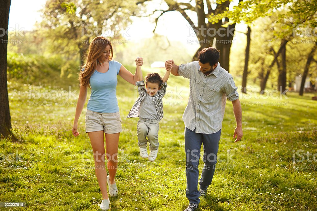 Happy family heaving fun in the park stock photo