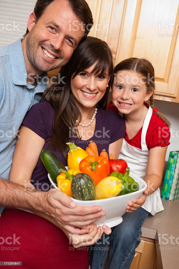Happy Family Holding a Big Bowl of Fresh Vegetables royalty-free stock photo