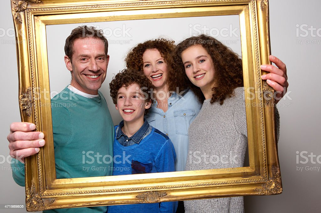 Happy family holding picture frame and smiling stock photo