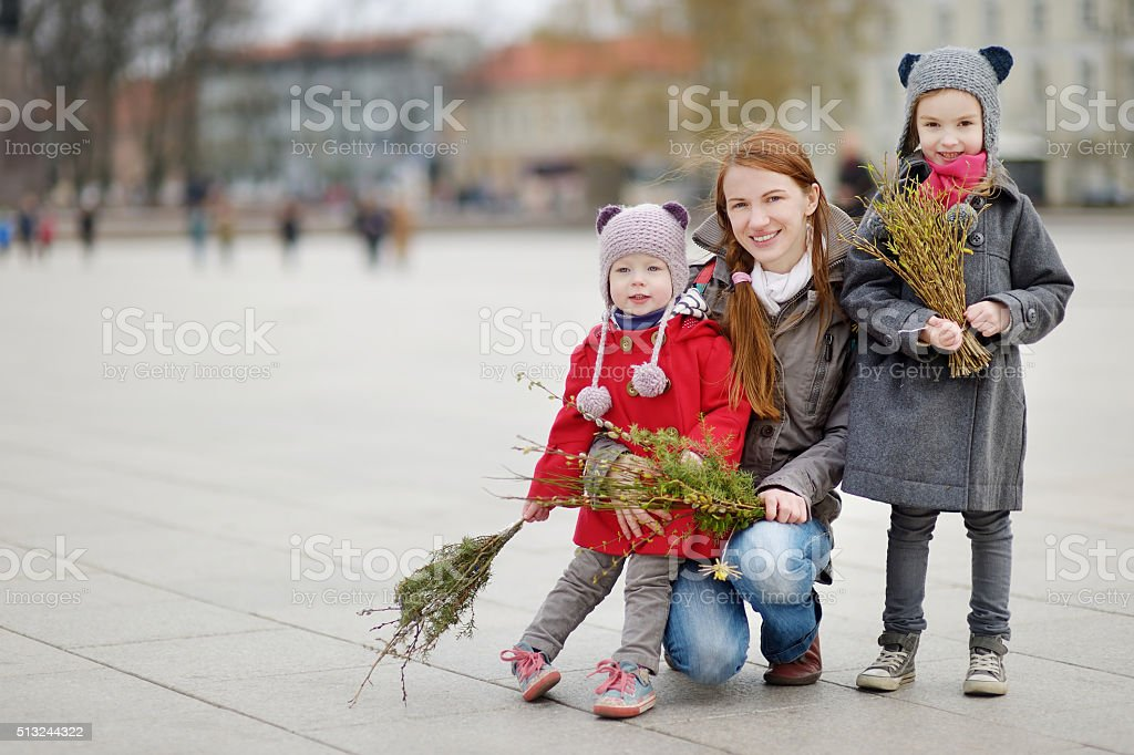 Happy family holding willow branches on Easter stock photo