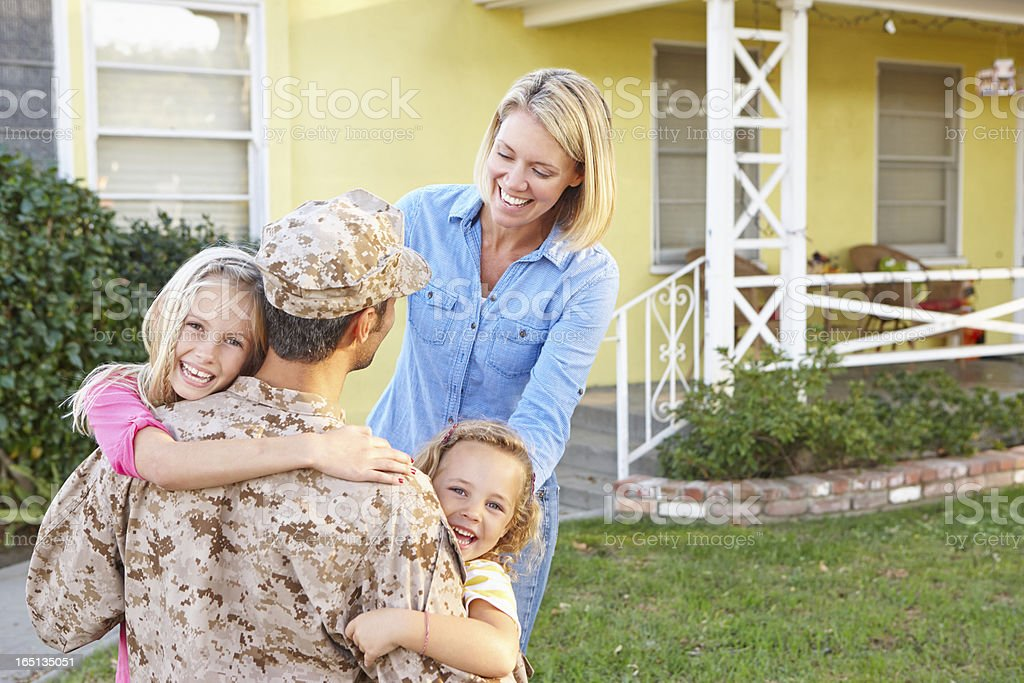 Happy family hugging army father who has returned home  stock photo