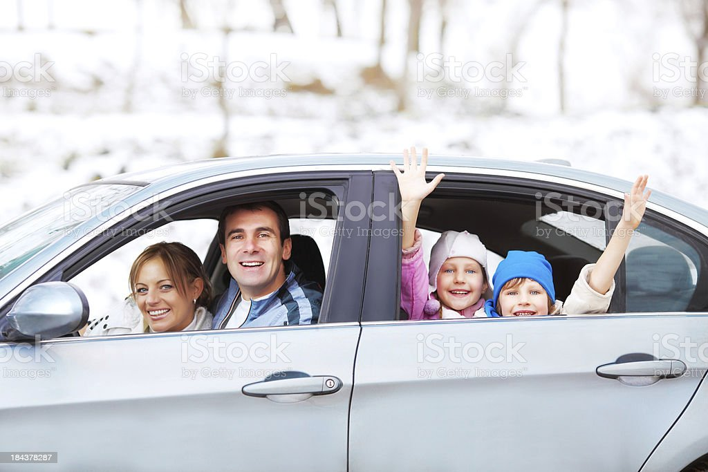 A happy family in a car against a snowy backdrop stock photo