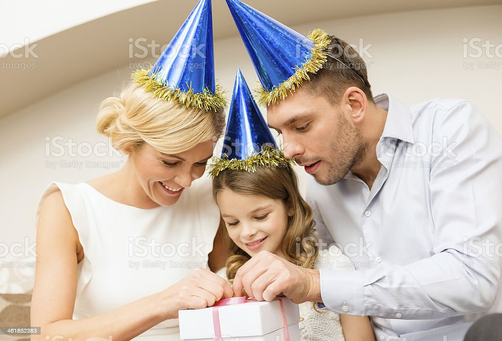 happy family in blue party hats opening gift box royalty-free stock photo