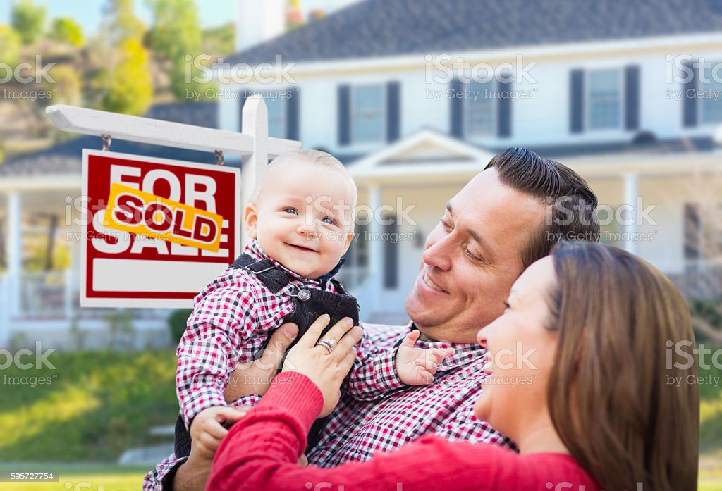 Happy Family In Front of For Sale Sign and House stock photo