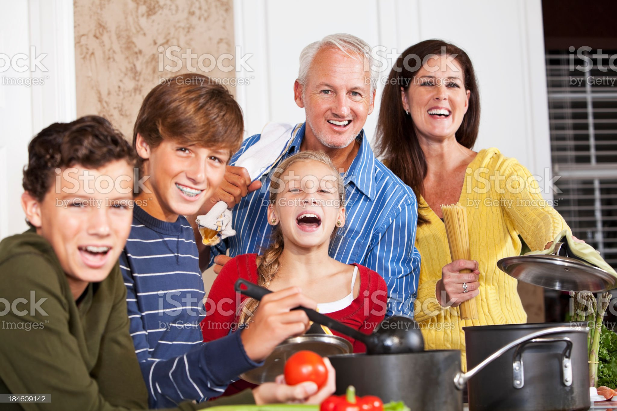 Happy family in kitchen by stove royalty-free stock photo