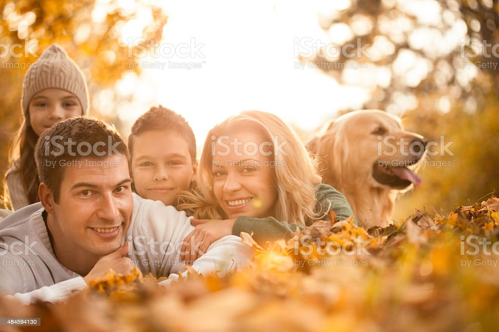Happy family in the autumn park with dog stock photo