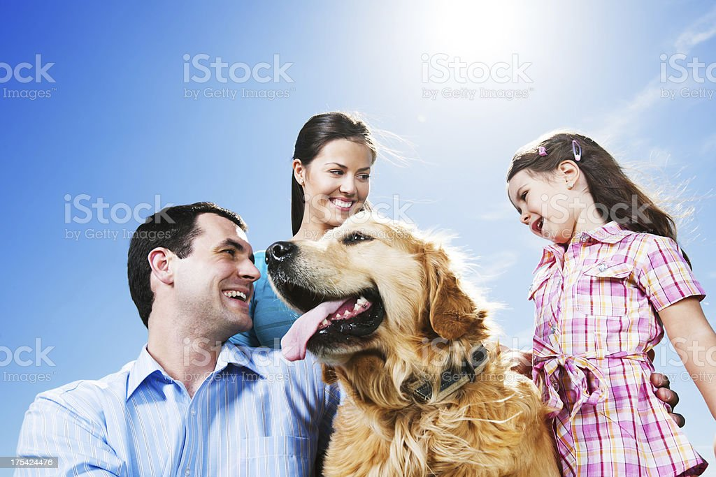 Happy family in the park with their dog. royalty-free stock photo