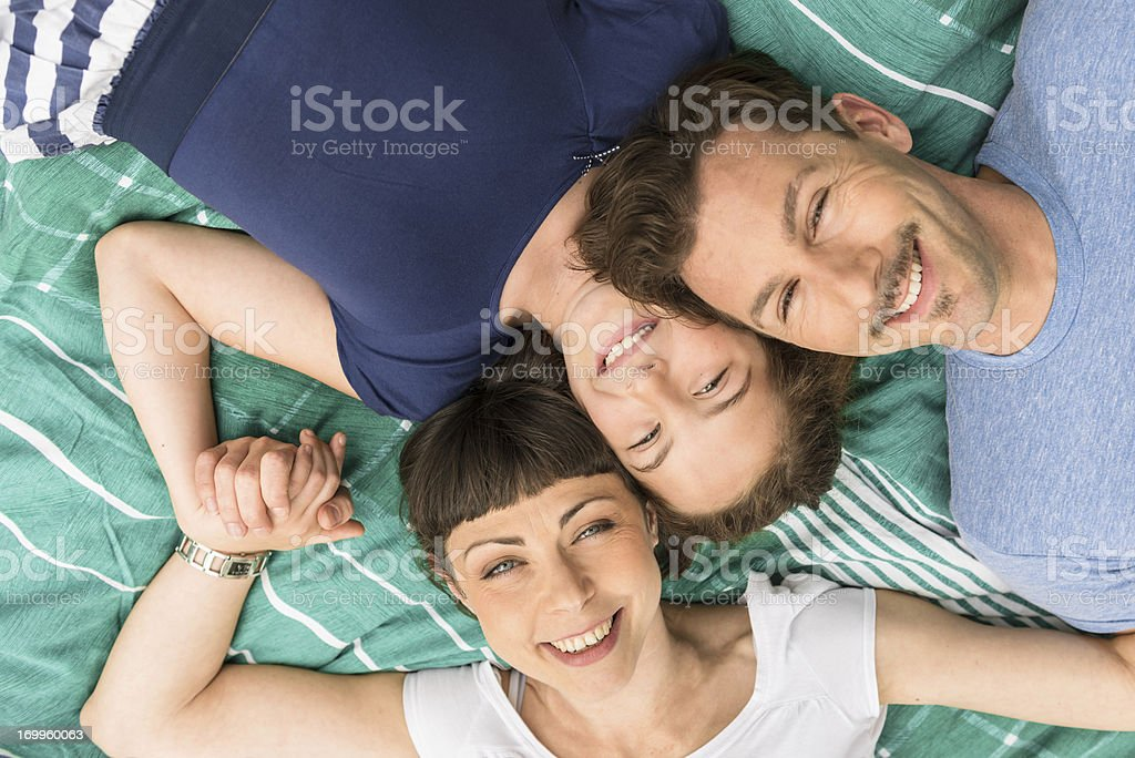 Happy family lying down and smiling royalty-free stock photo