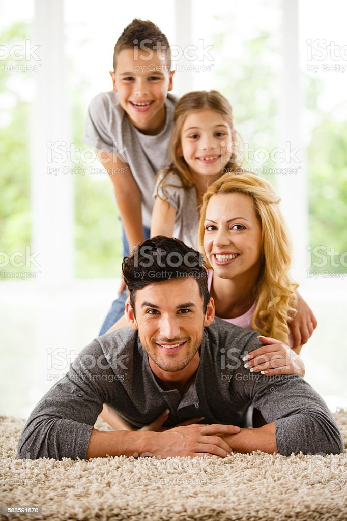 Happy family lying down on the floor at home stock photo