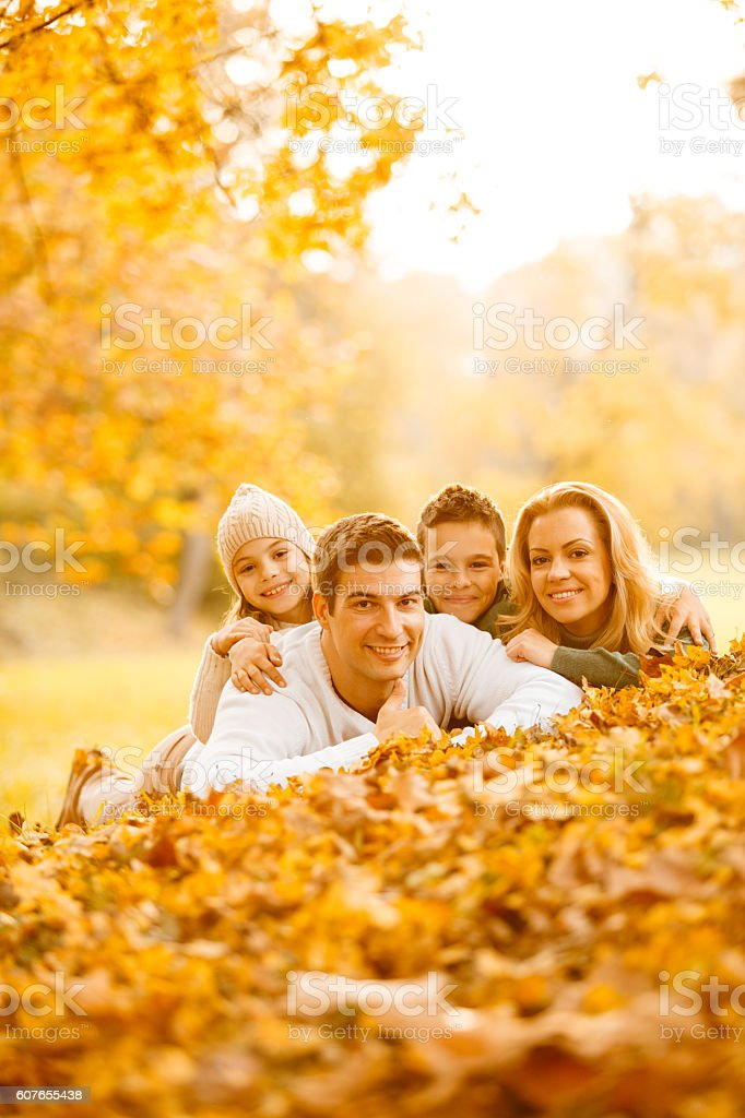 Happy family lying in autumn leaves stock photo
