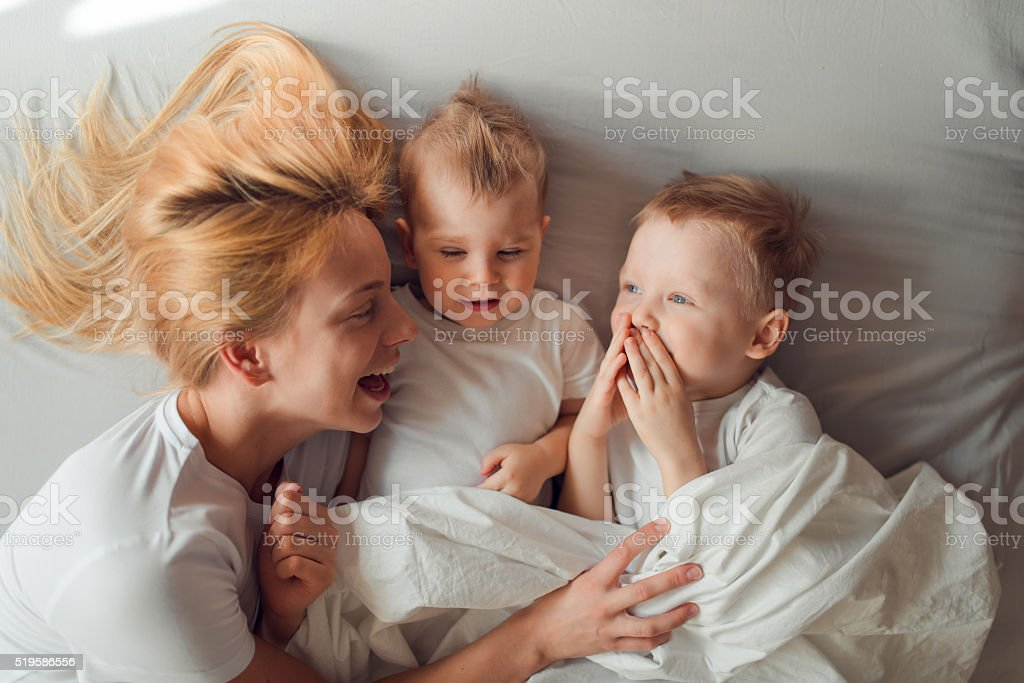 Happy family lying in bed in the morning stock photo