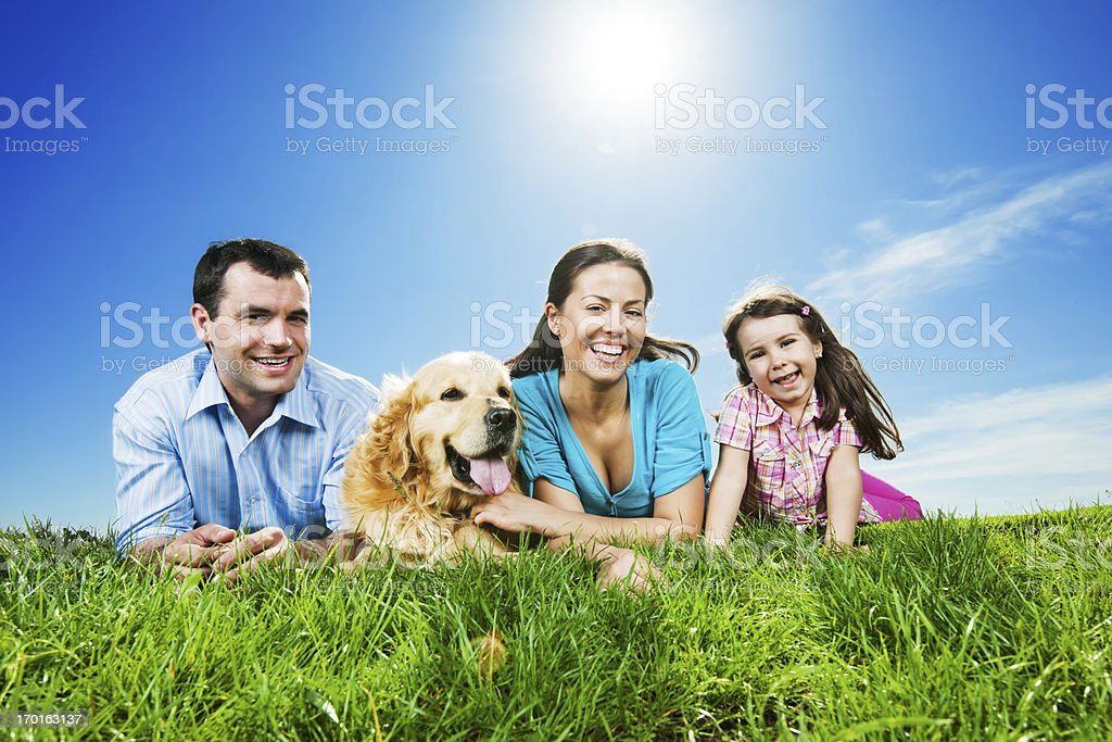Happy family lying in the park with their dog. royalty-free stock photo