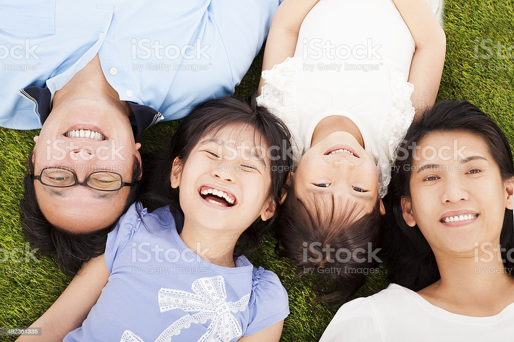 happy family lying on a meadow together stock photo