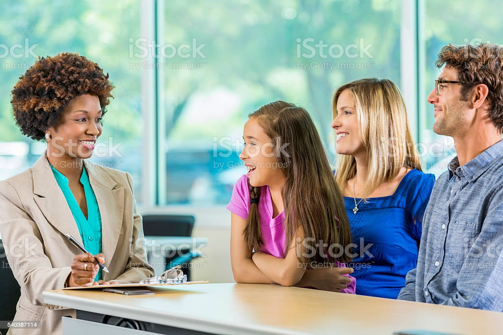 Happy family meeting with African American Teacher stock photo