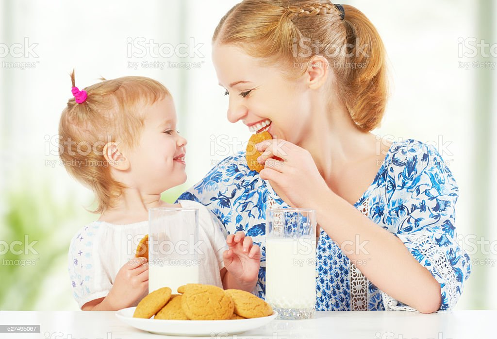 happy family mother and baby daughter at biscuits with milk stock photo