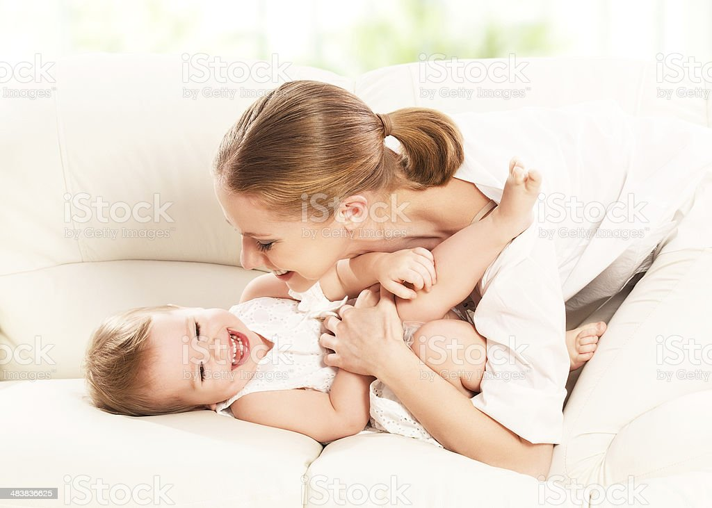 happy family. Mother and baby daughter plays  on the sofa stock photo