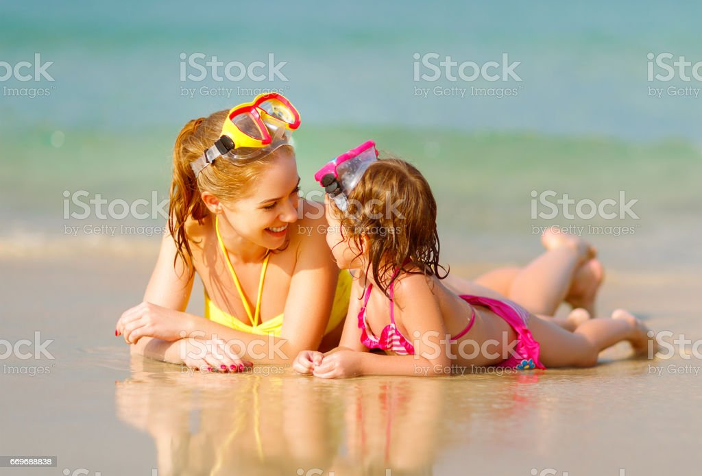 Happy family mother and chid daughter in masks on beach in summer stock photo