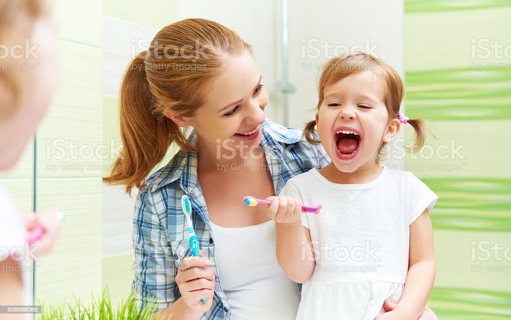 happy family mother and child girl cleans teeth with toothbrush stock photo