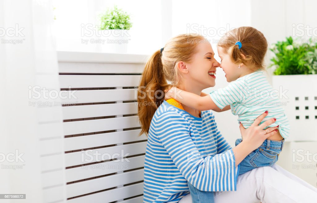 Happy family mother and child hugging and laughing stock photo