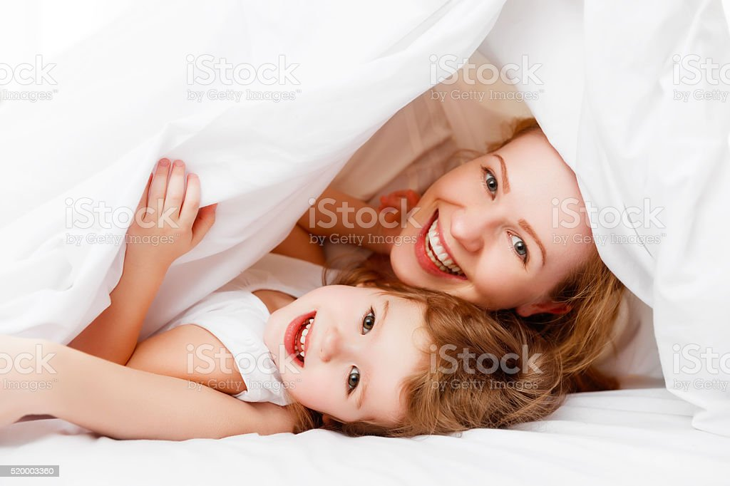 happy family mother and child playing and laughing in bed stock photo
