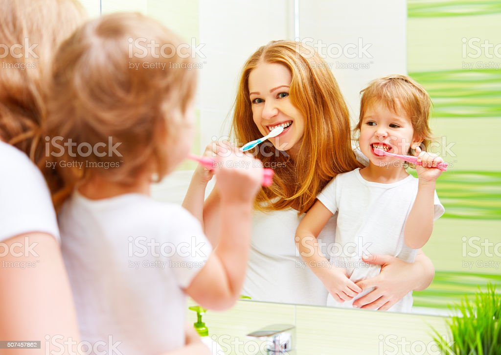 happy family mother and daughter child brushing her teeth toothb stock photo