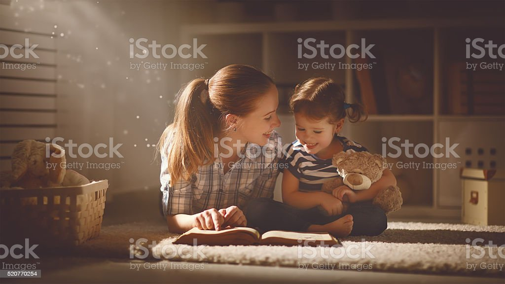 happy family mother and daughter read a book in evening stock photo