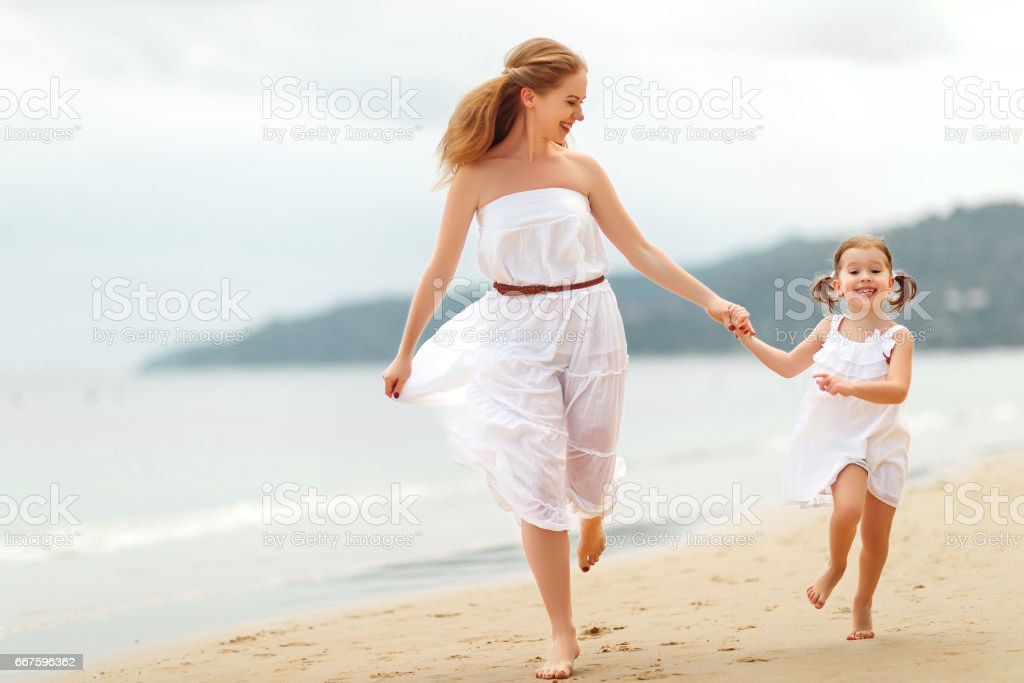 happy family  mother and daughter run, laugh and play at beach stock photo