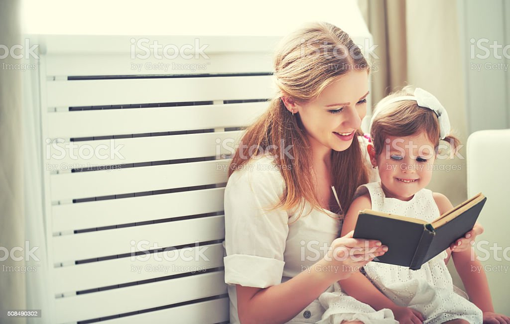 happy family mother child little girl reading  book stock photo