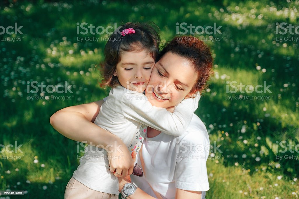Happy family, mother hugs her daughter. stock photo